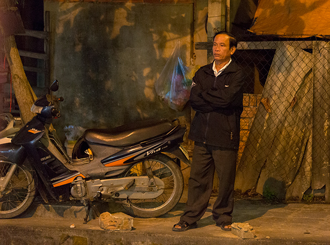 A man waiting next to a motorbike