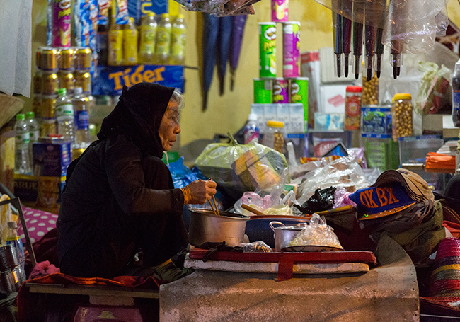 The old woman had her dinner while she is waiting for customers on the side of the street